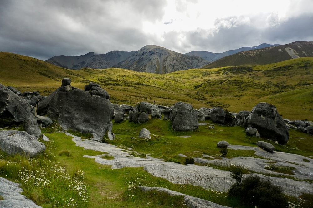 gray rocks on green grass field near mountain under white clouds during daytime