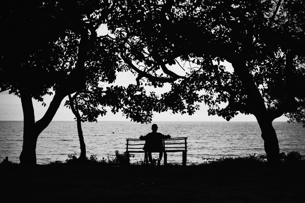 silhouette of man sitting on bench near body of water during daytime