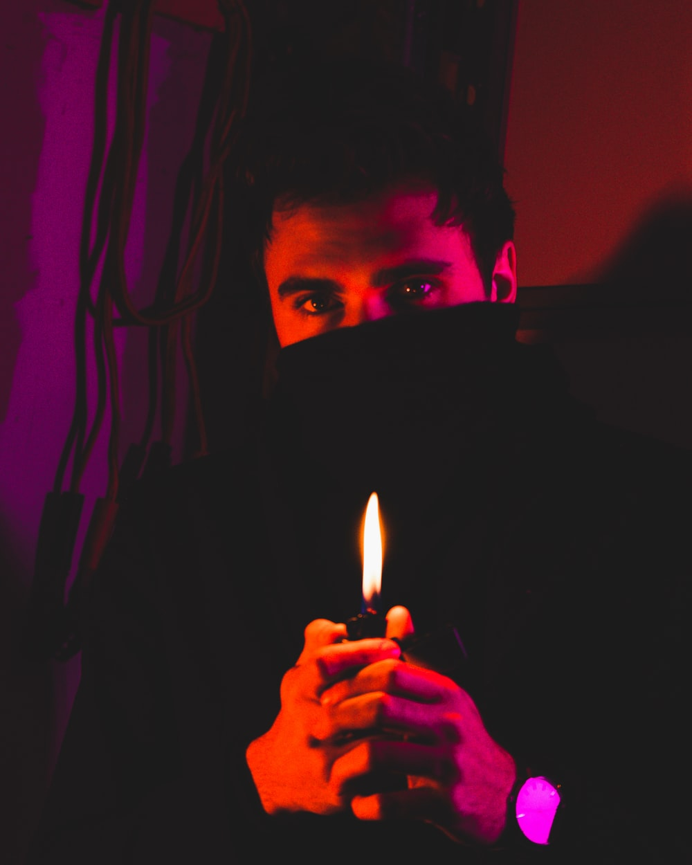 man in black hoodie holding lighted candle