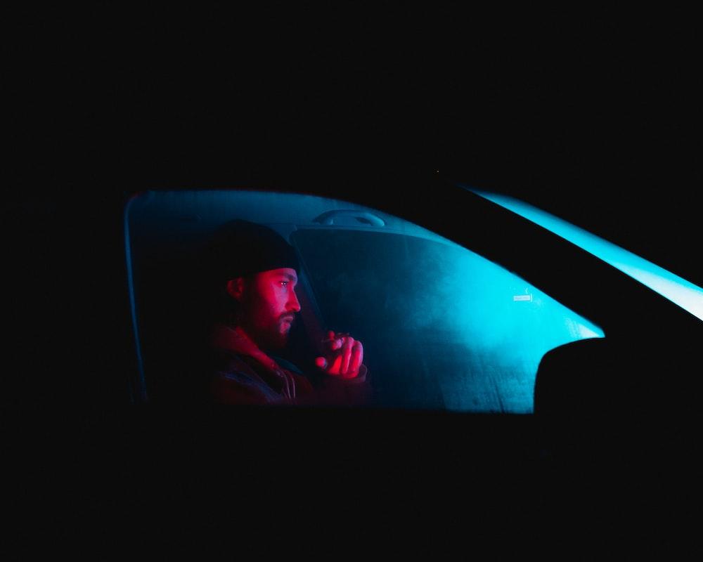 man in red shirt inside car