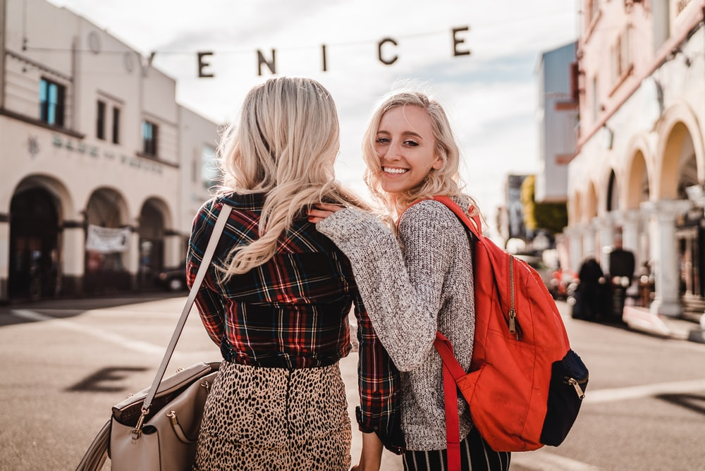 woman in black and white long sleeve shirt carrying girl in red jacket