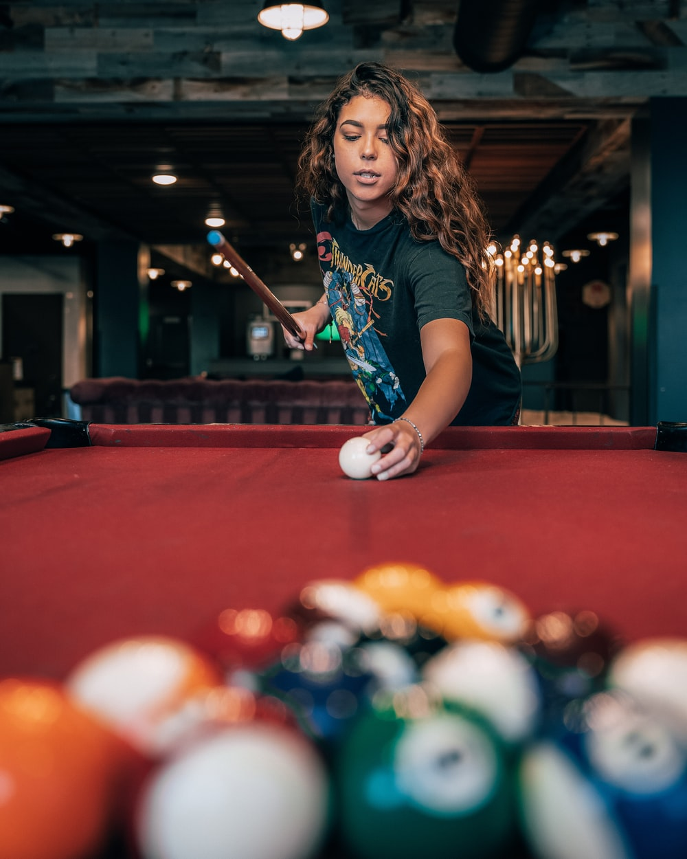 girl in blue and white crew neck t-shirt playing billiard