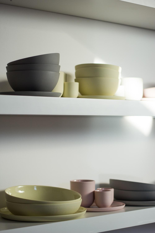 white ceramic bowls on white wooden shelf