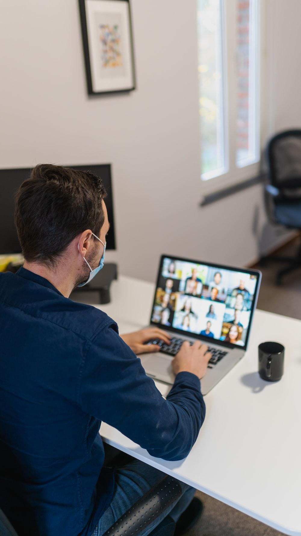 man in blue long sleeve shirt using black laptop computer