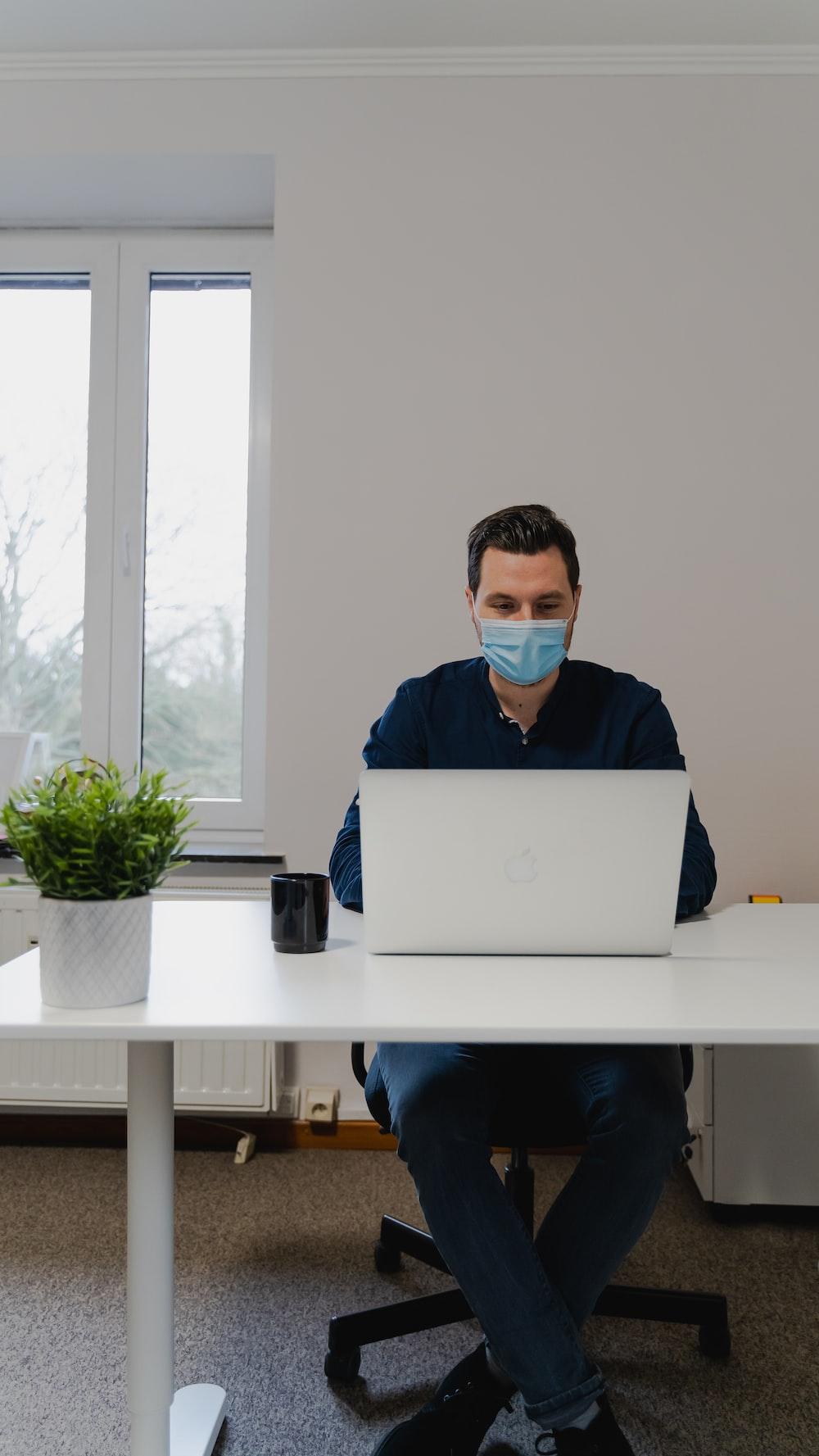 man in blue dress shirt using silver macbook