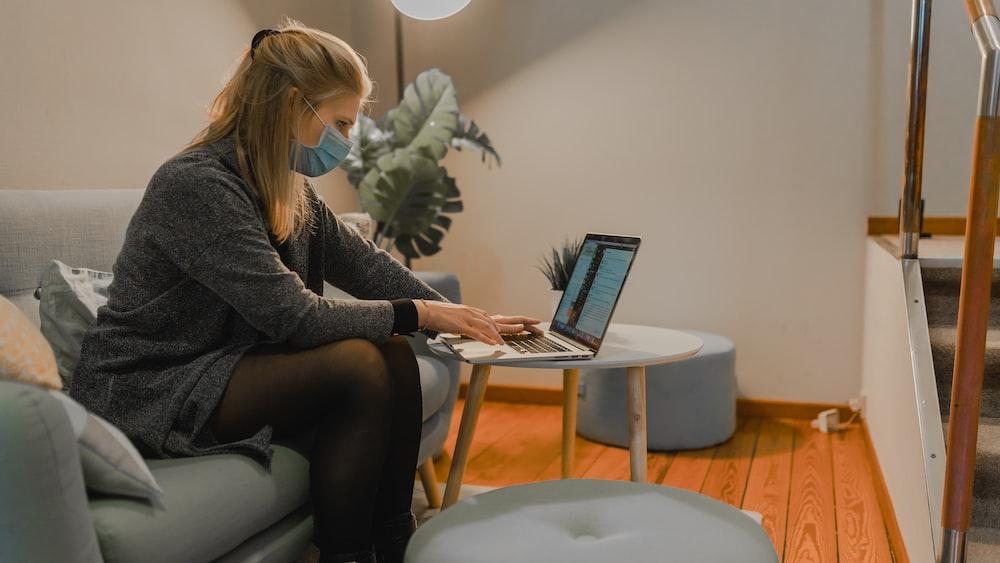 woman in gray sweater using macbook air