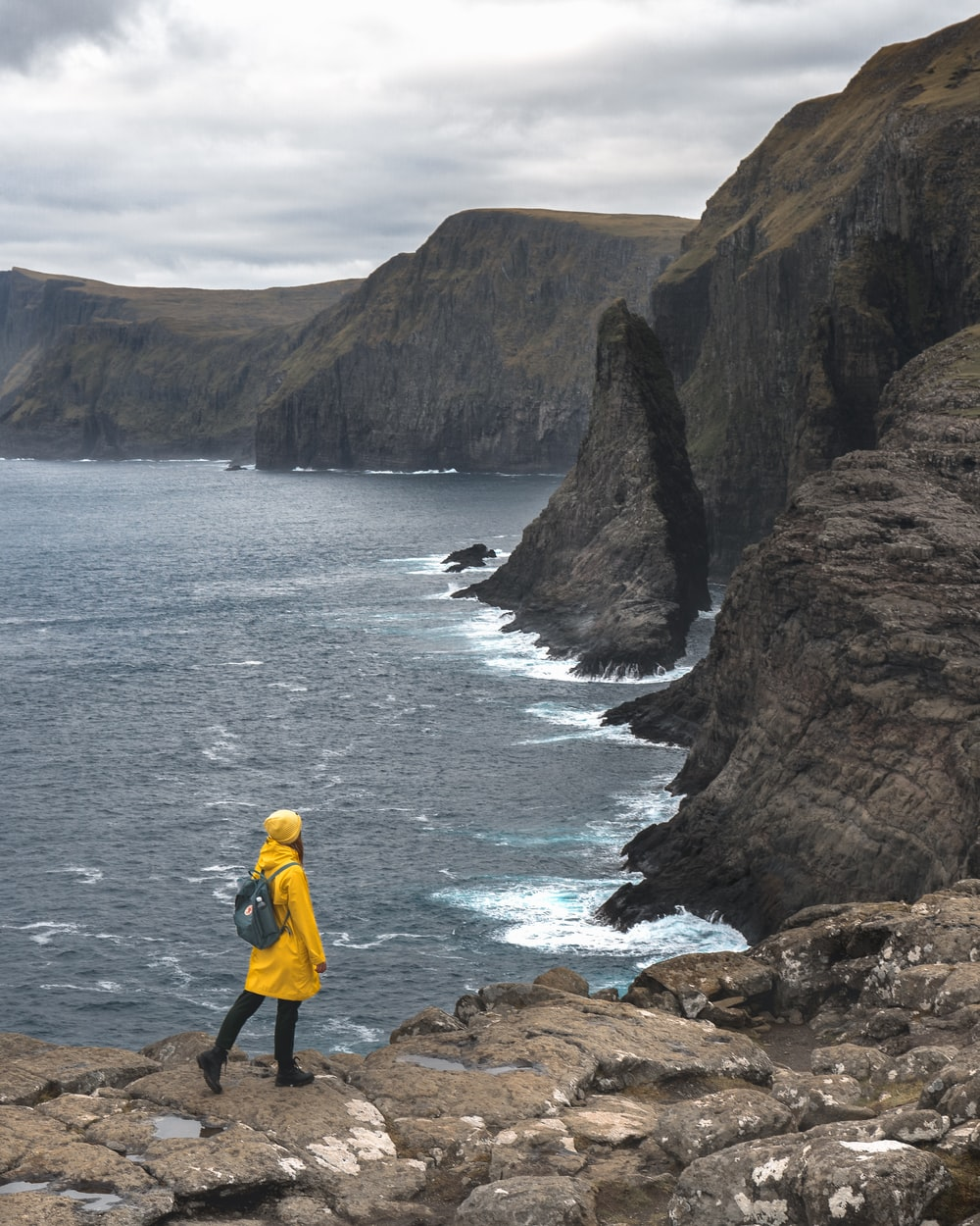 man in yellow jacket and black pants standing on brown rock formation near body of water