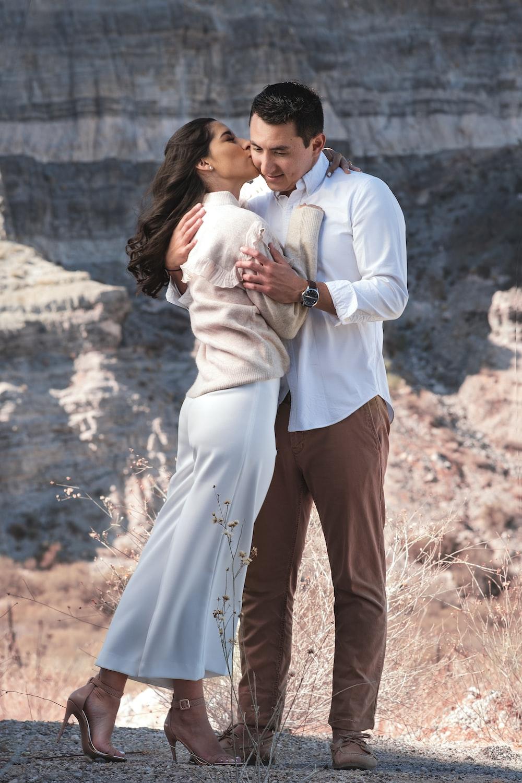 man in white dress shirt carrying woman in white dress