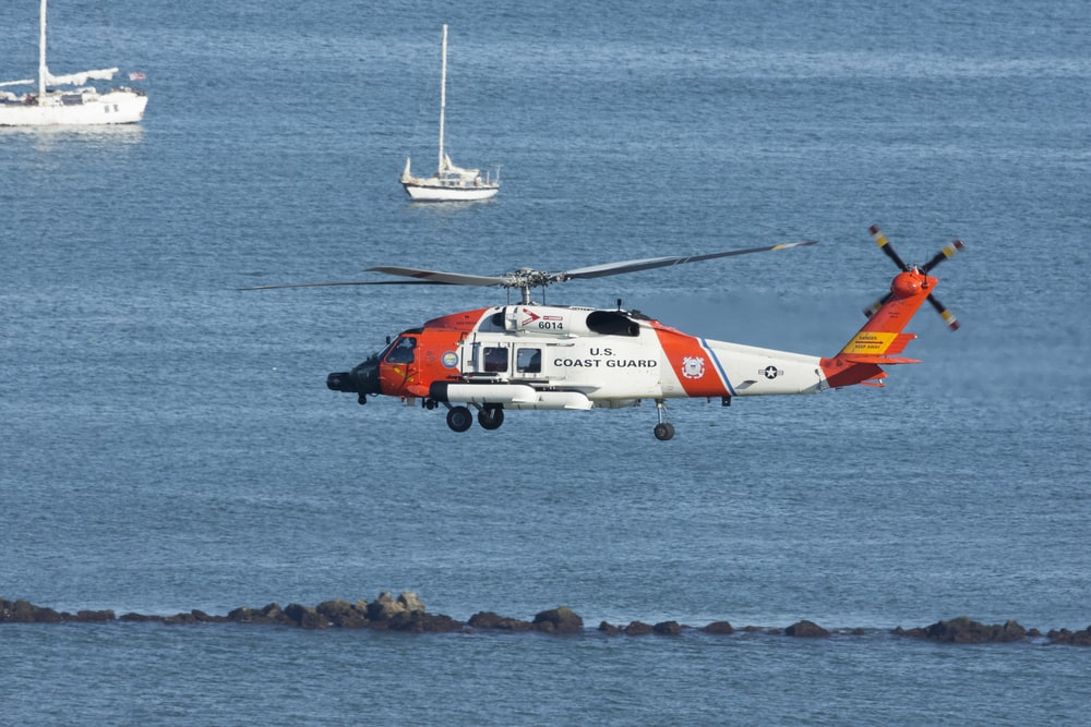 white and orange helicopter on body of water during daytime