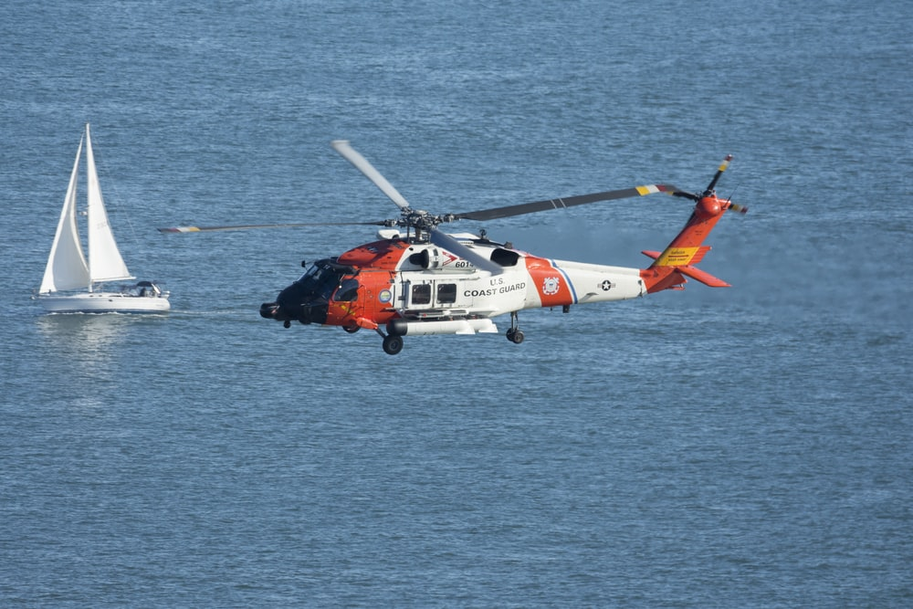 orange and white helicopter flying over the sea during daytime