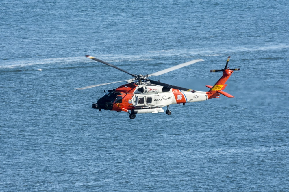 orange and white helicopter on body of water during daytime