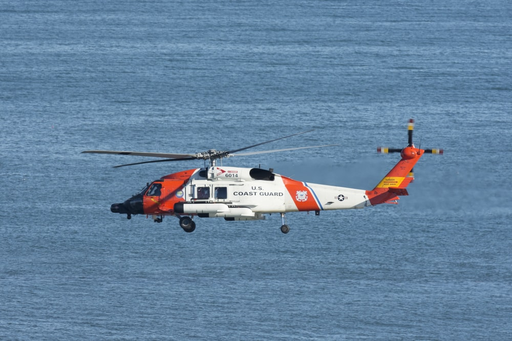 white and orange helicopter flying over the sea during daytime