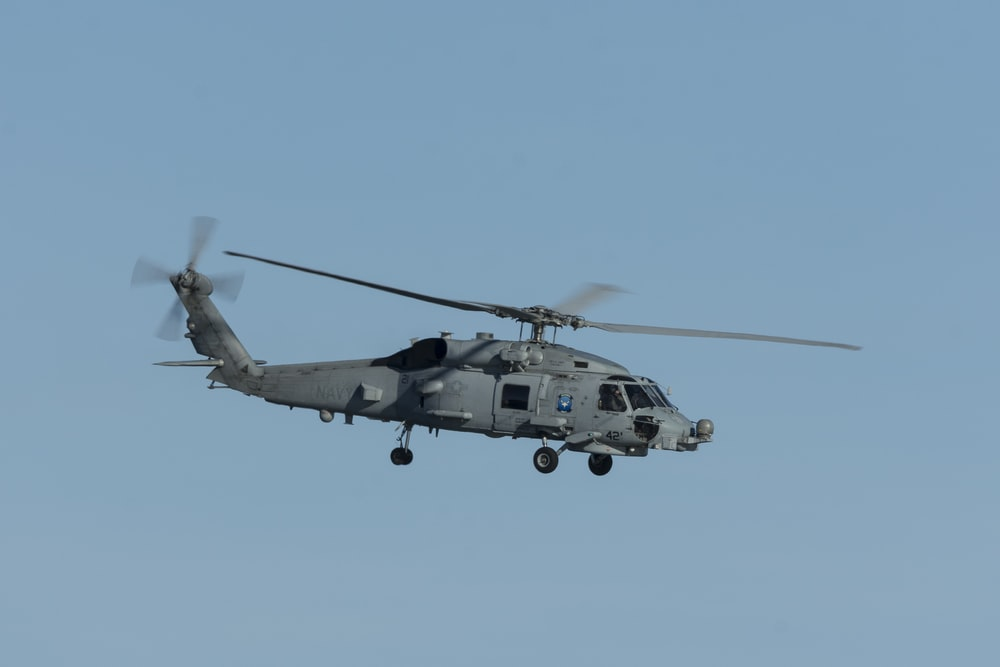 white and black helicopter flying in the sky during daytime