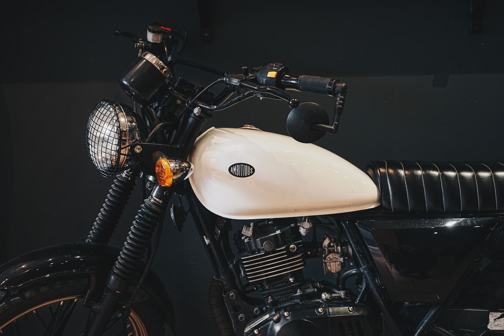 white and black motorcycle in a dark room