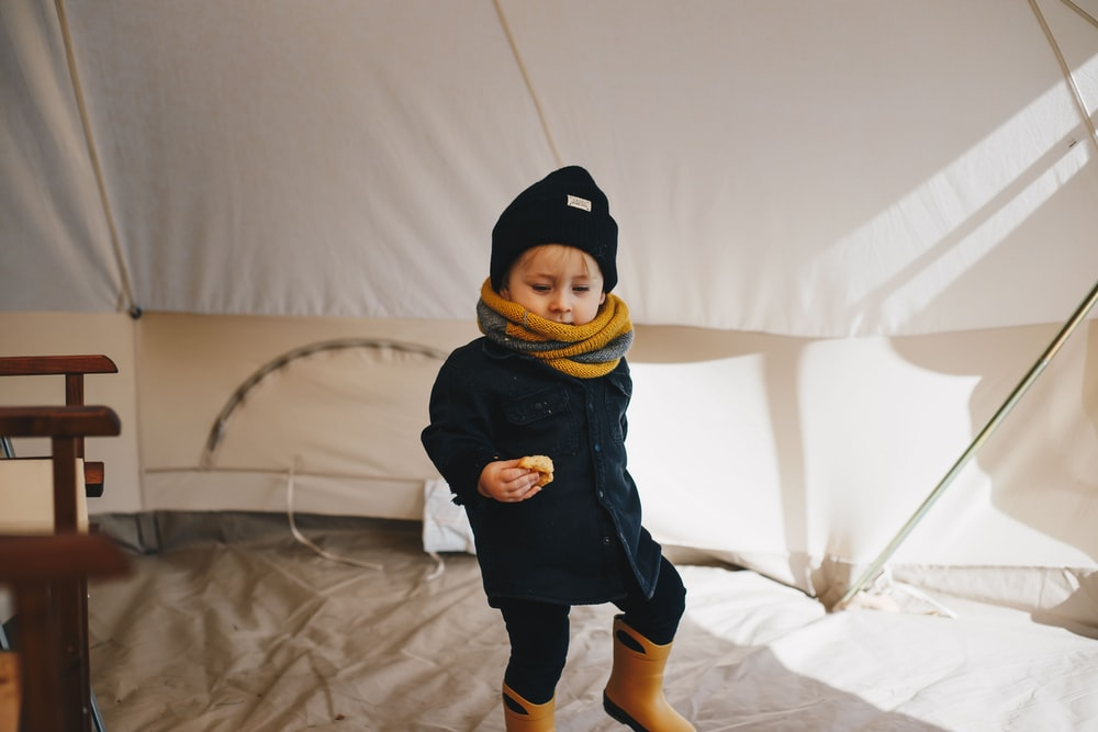 child in black and yellow hoodie standing on white textile