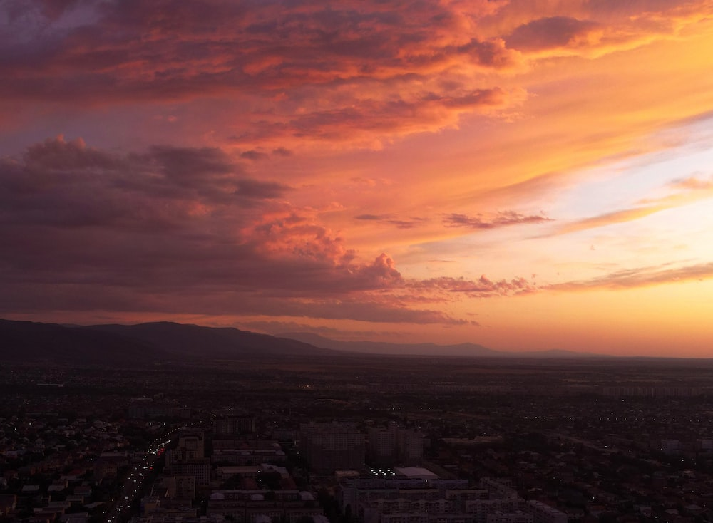 city skyline under orange and gray cloudy sky during sunset
