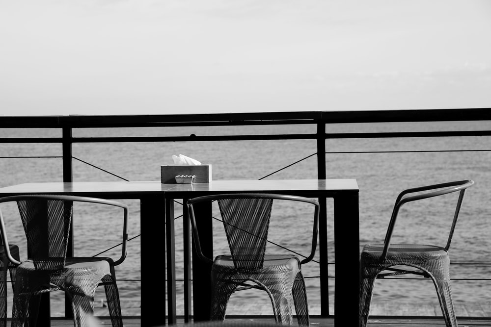 grayscale photo of a table and chairs