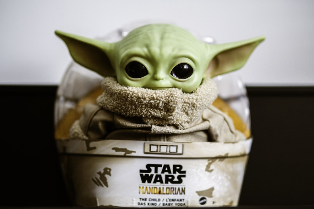green frog figurine in brown cardboard box