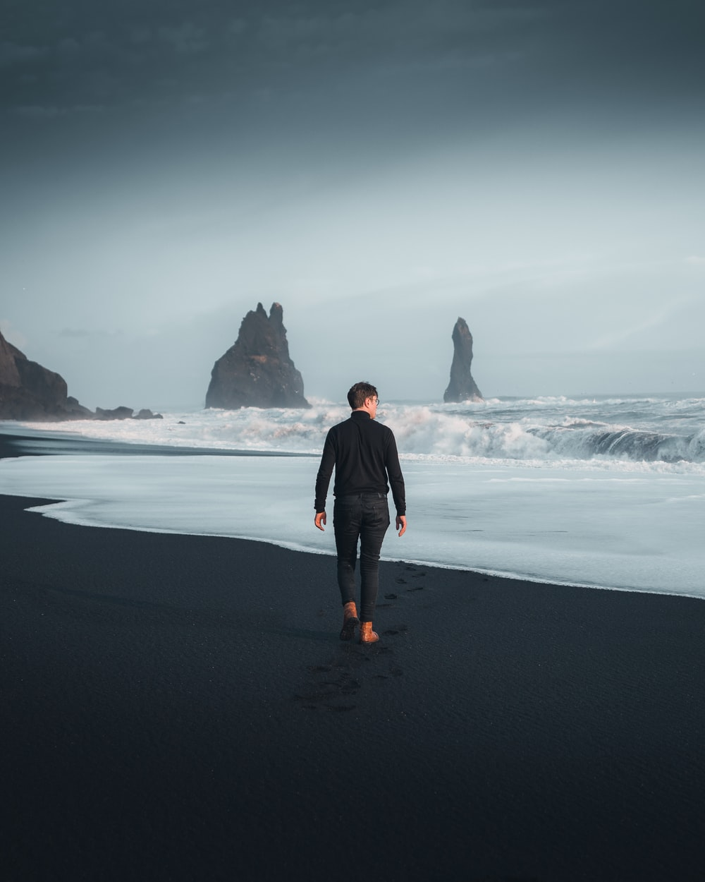 man in black jacket standing on seashore during daytime