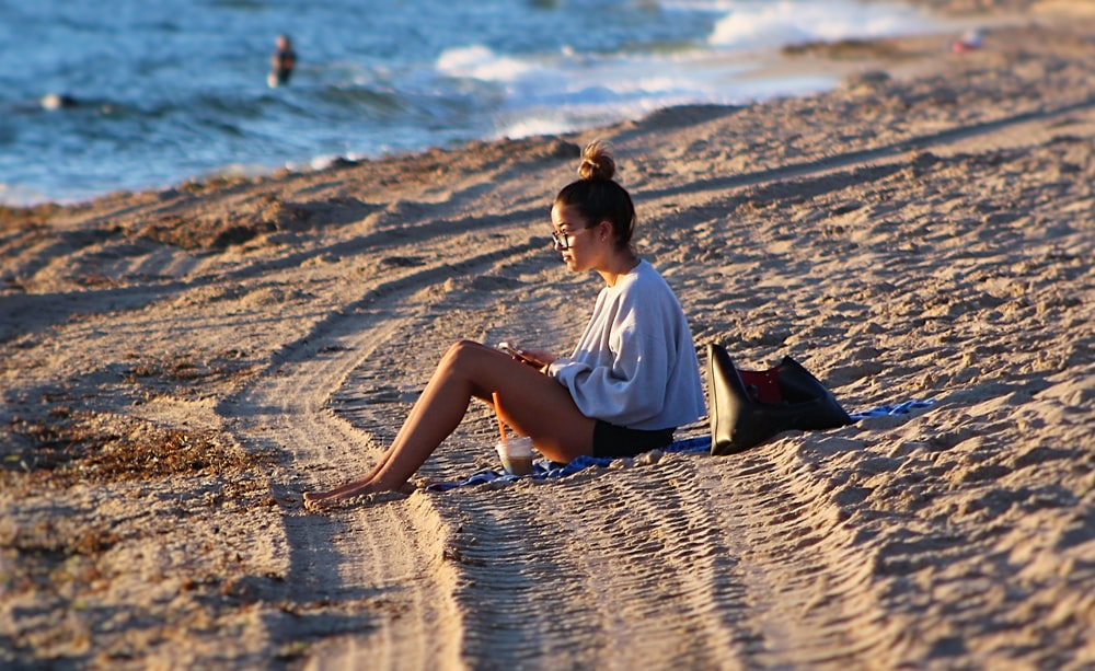 woman in white shirt sitting on beach during daytime
