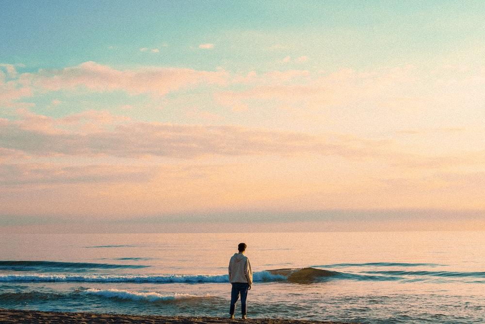 man in white long sleeve shirt standing on seashore during daytime