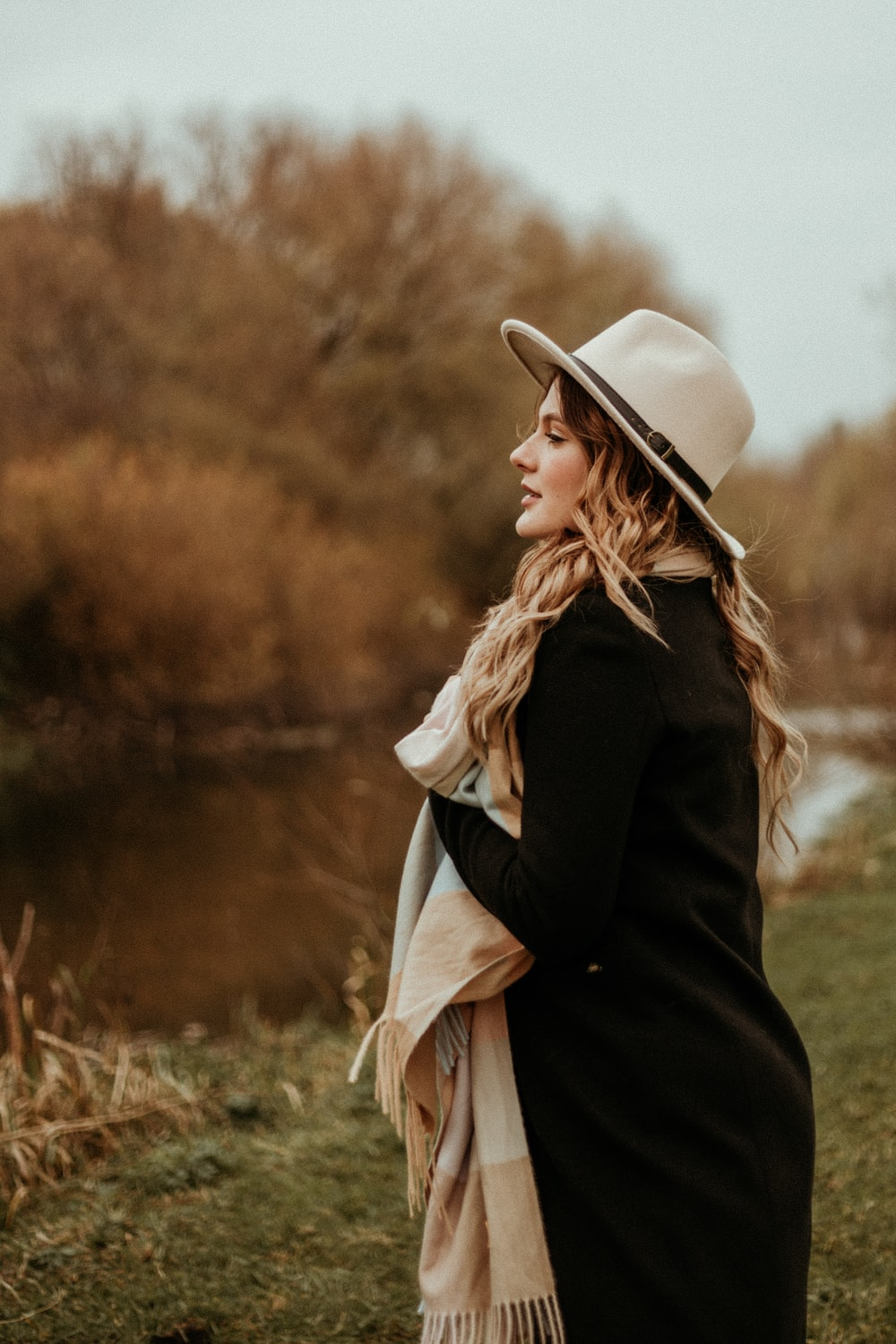 woman in black coat and white sun hat standing on green grass field during daytime