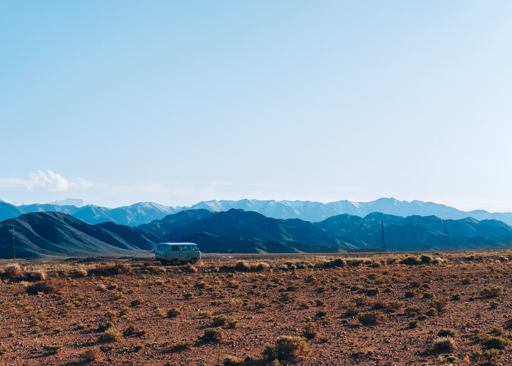 brown field near mountains during daytime