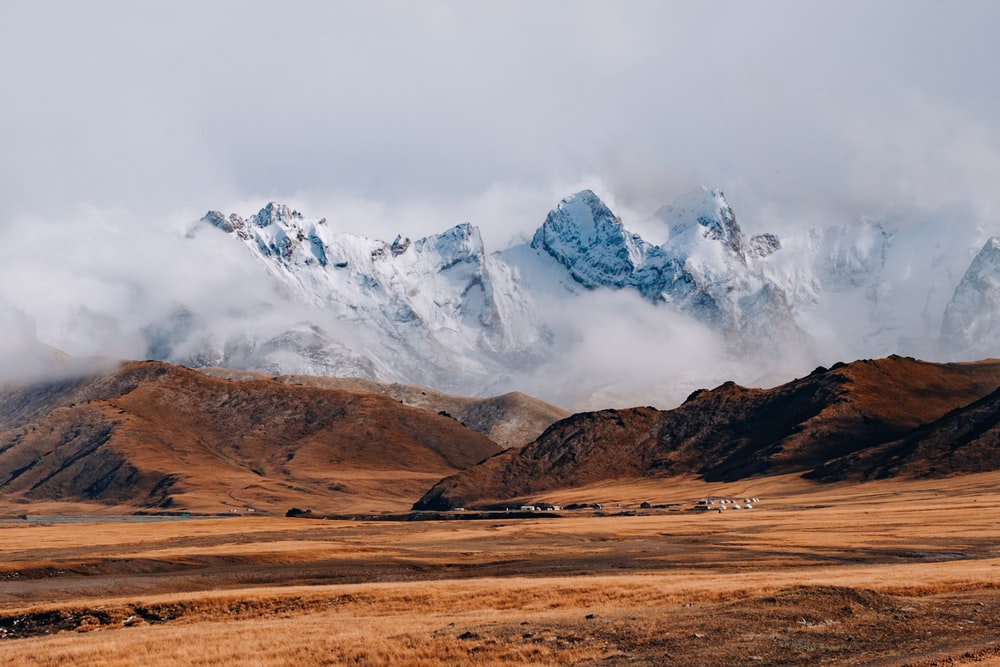 brown and white mountains under white clouds during daytime