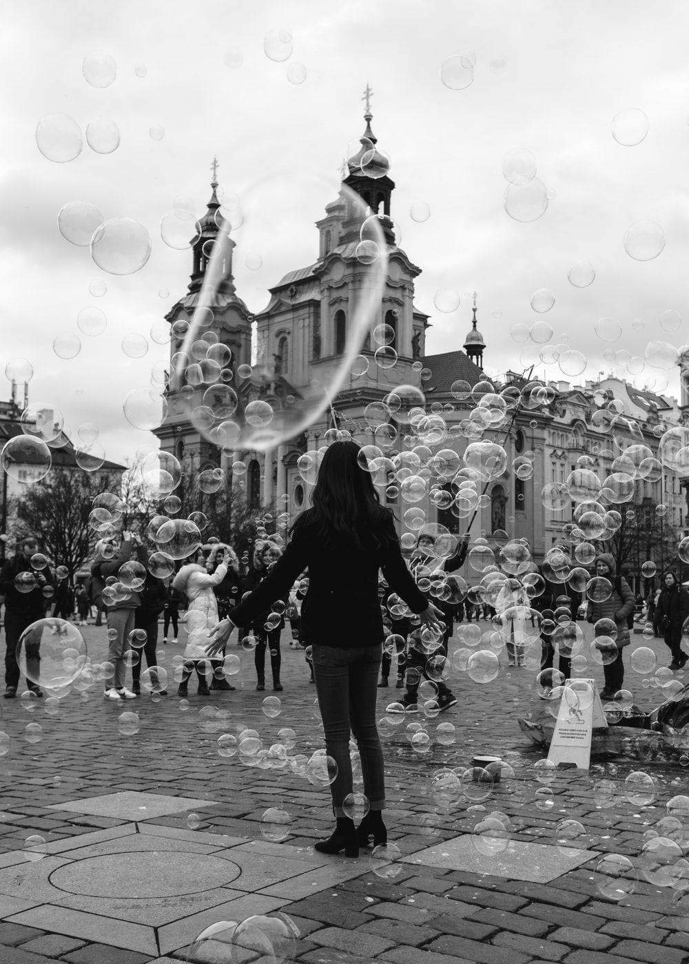grayscale photo of woman in black jacket and pants standing on street with bubbles