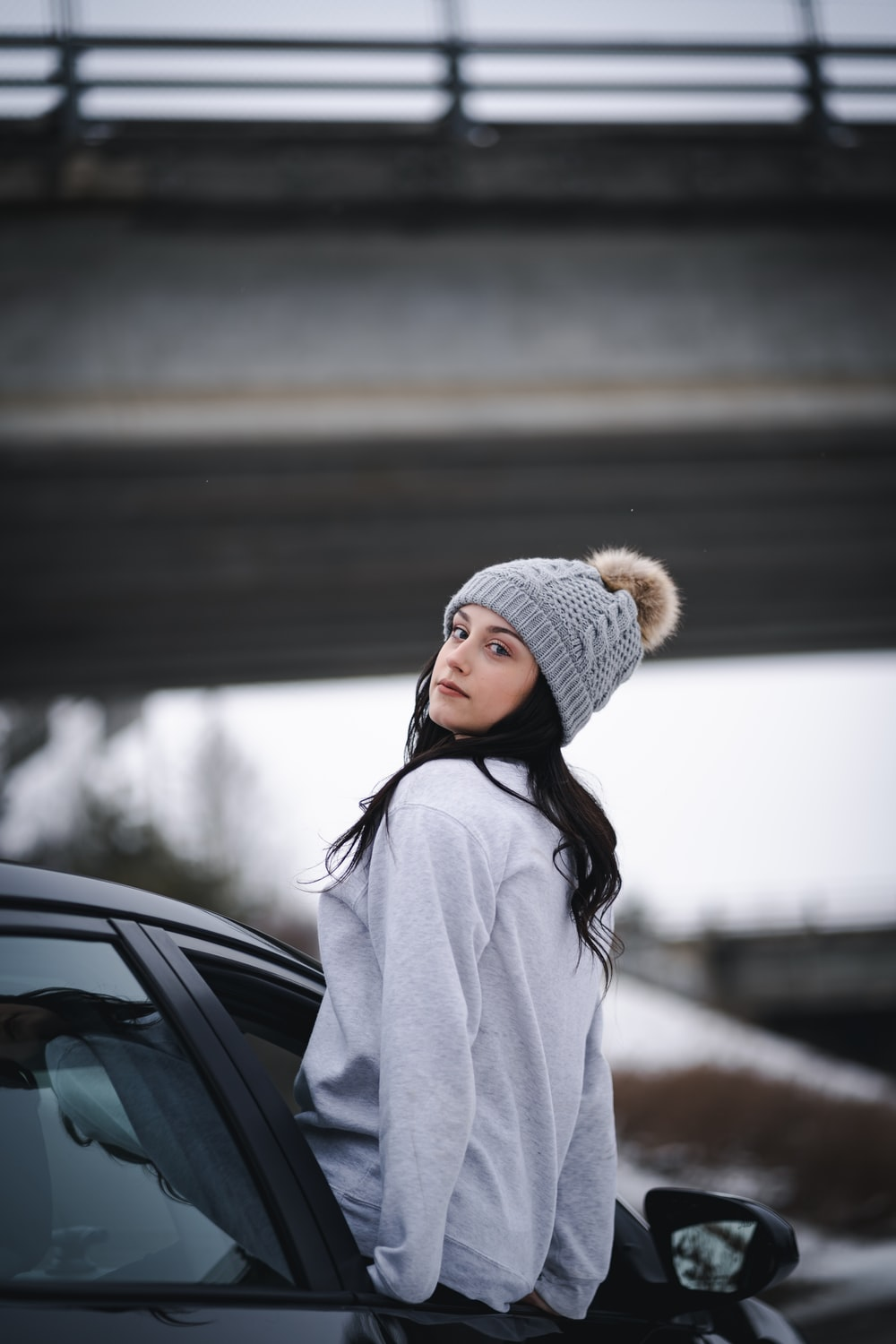 woman in white knit cap and white coat standing beside black car during daytime