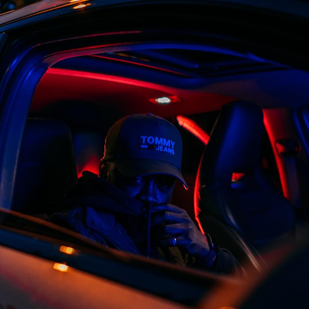 man in black jacket wearing black cap driving car