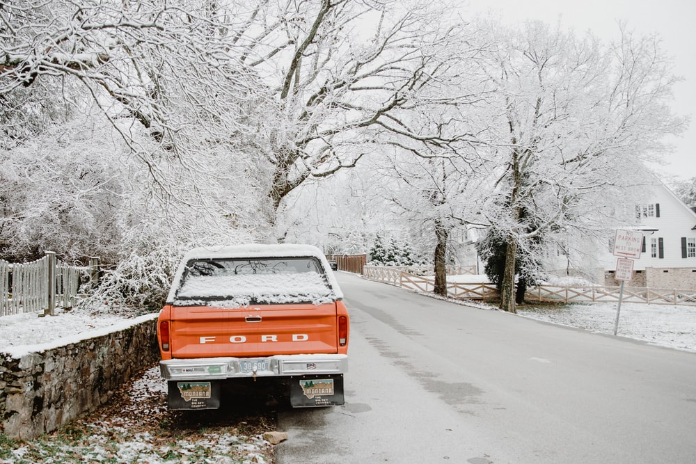 red and white chevrolet truck on snow covered road during daytime