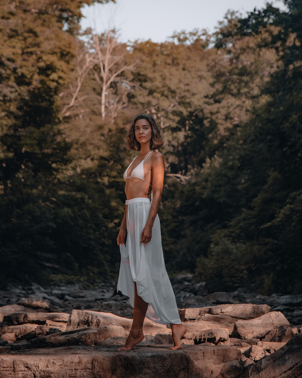 woman in white spaghetti strap dress standing on brown rock during daytime