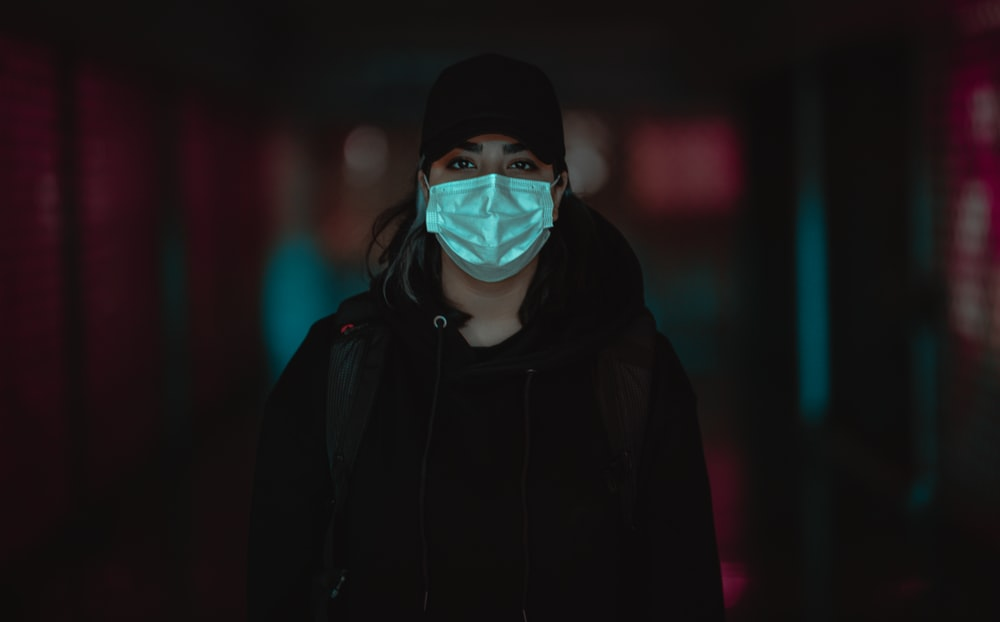 man in black hoodie wearing white mask
