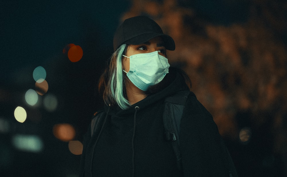 woman in black hoodie wearing white mask