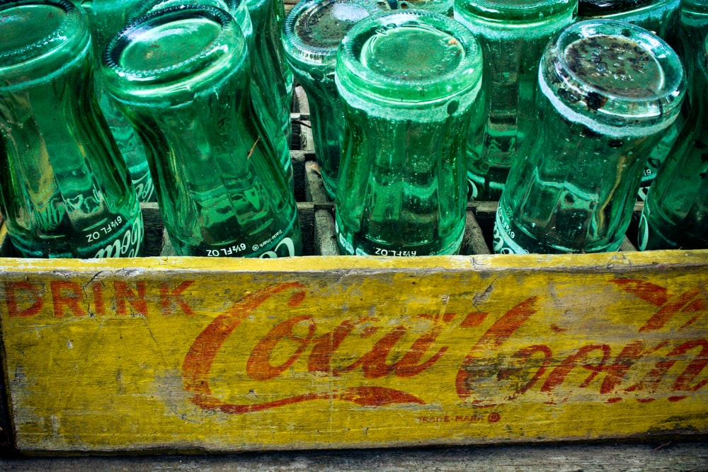 green glass bottles on brown wooden crate