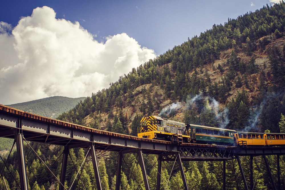 yellow and blue train on rail tracks near green trees under white clouds and blue sky
