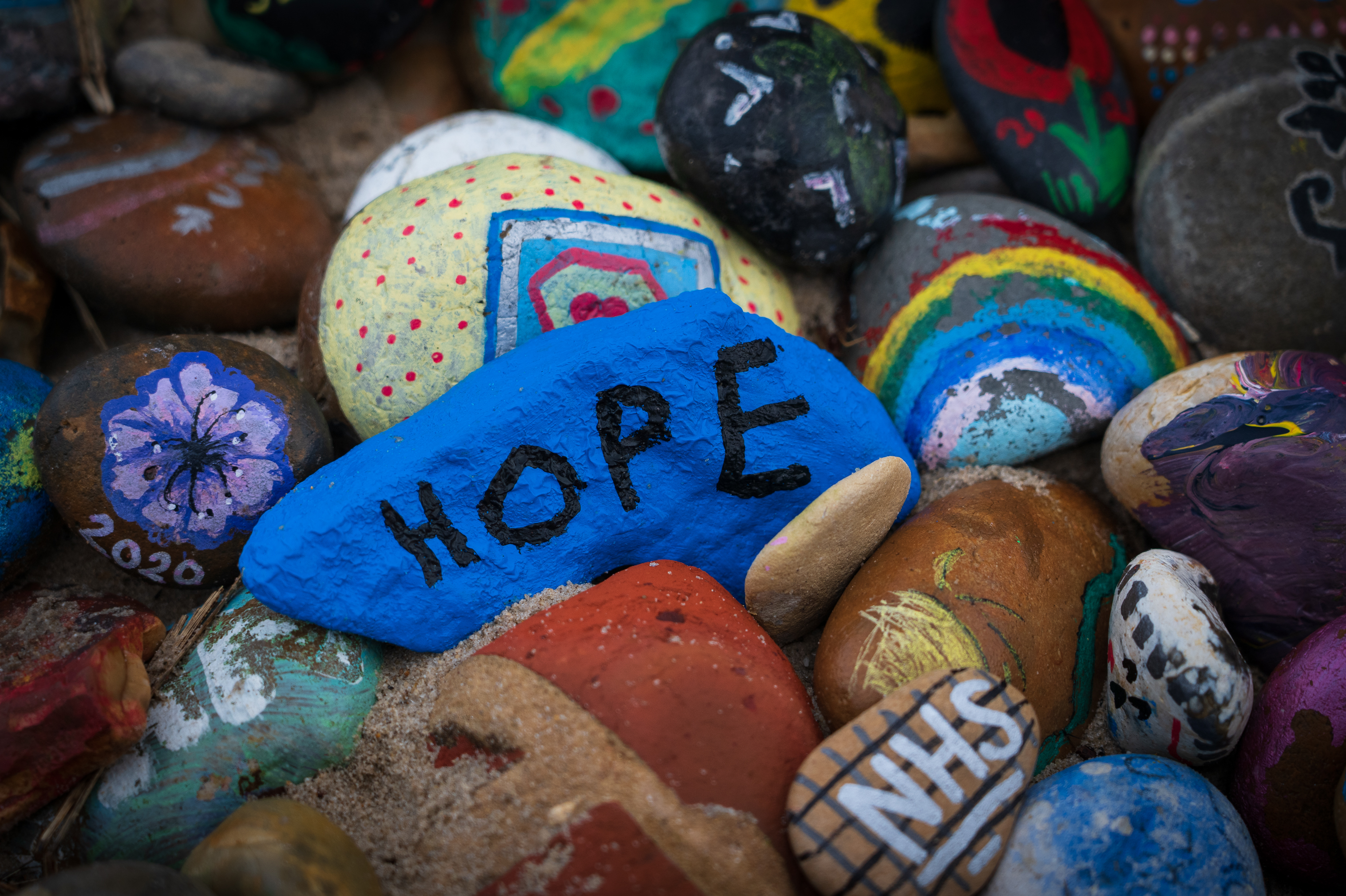 A pebble painted blue, with the word hope written on it in black.