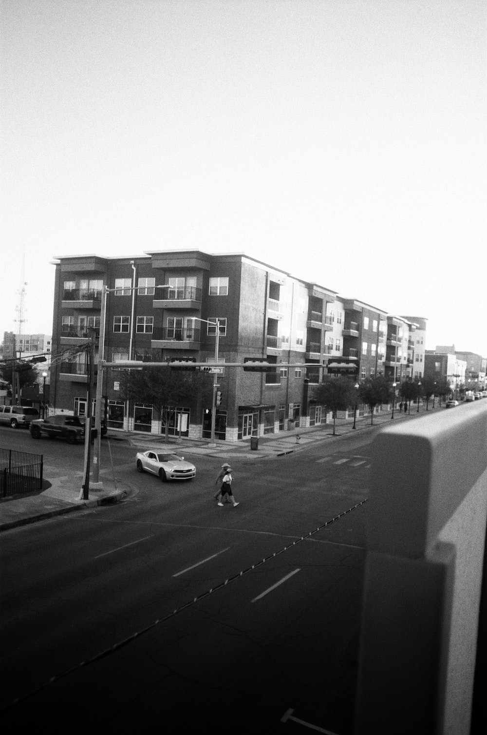 grayscale photo of cars on road near buildings
