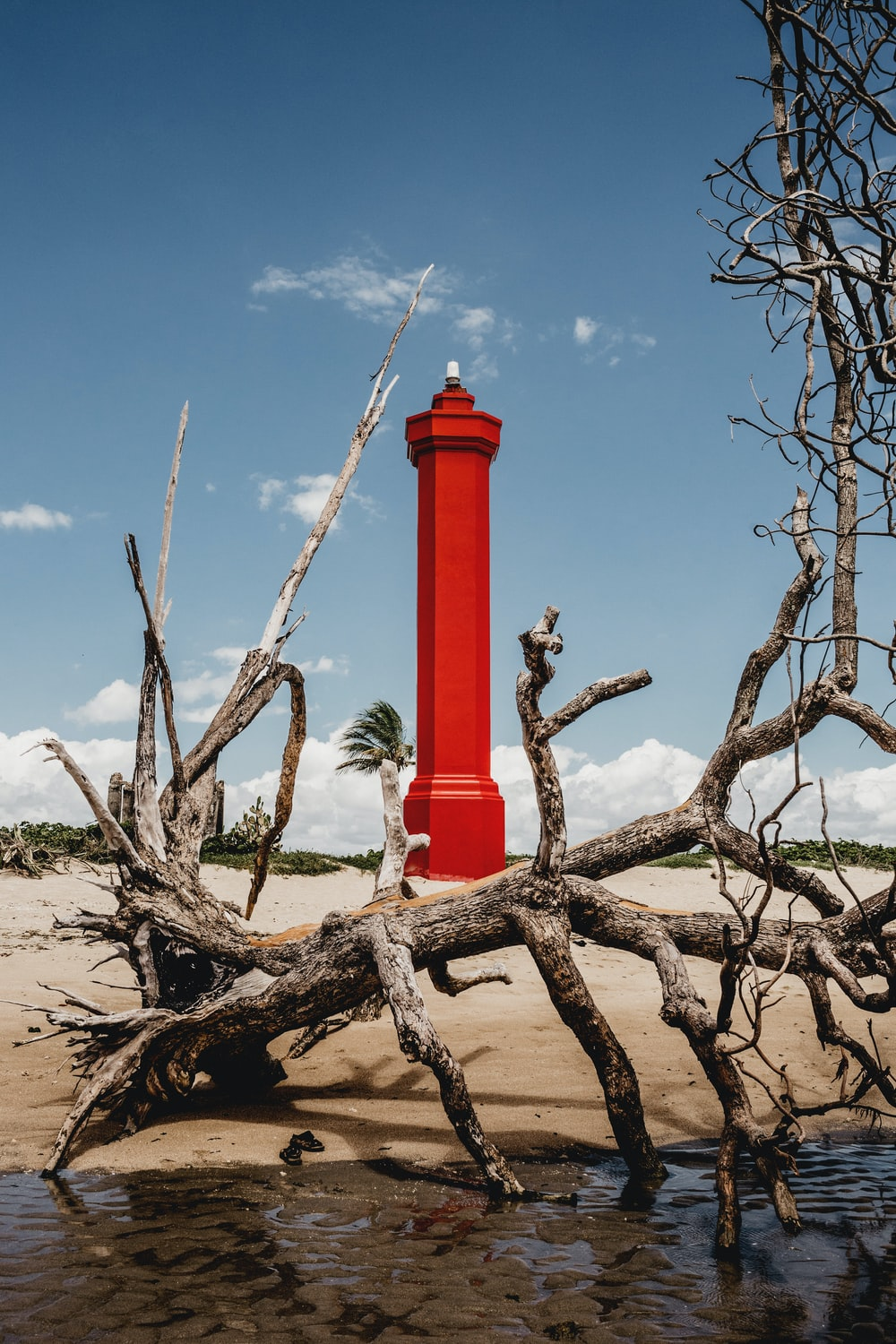 red and white concrete lighthouse under blue sky during daytime