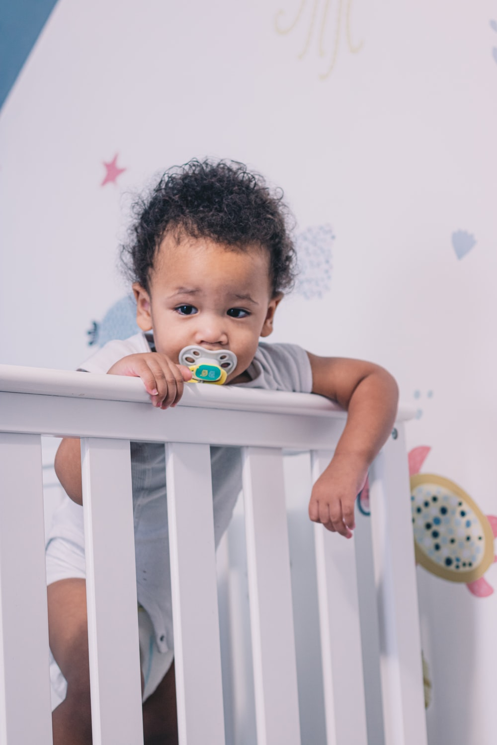 baby in white crib with pacifier