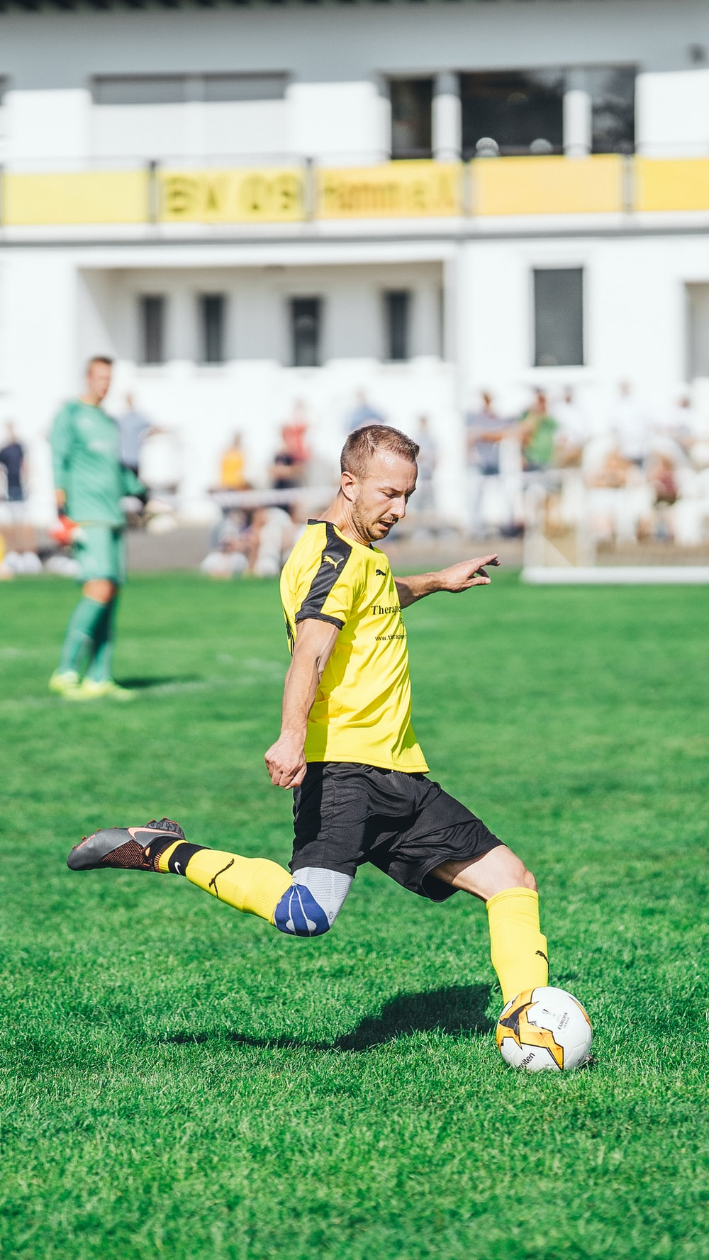 boy in yellow and black soccer jersey kicking soccer ball on green grass field during daytime