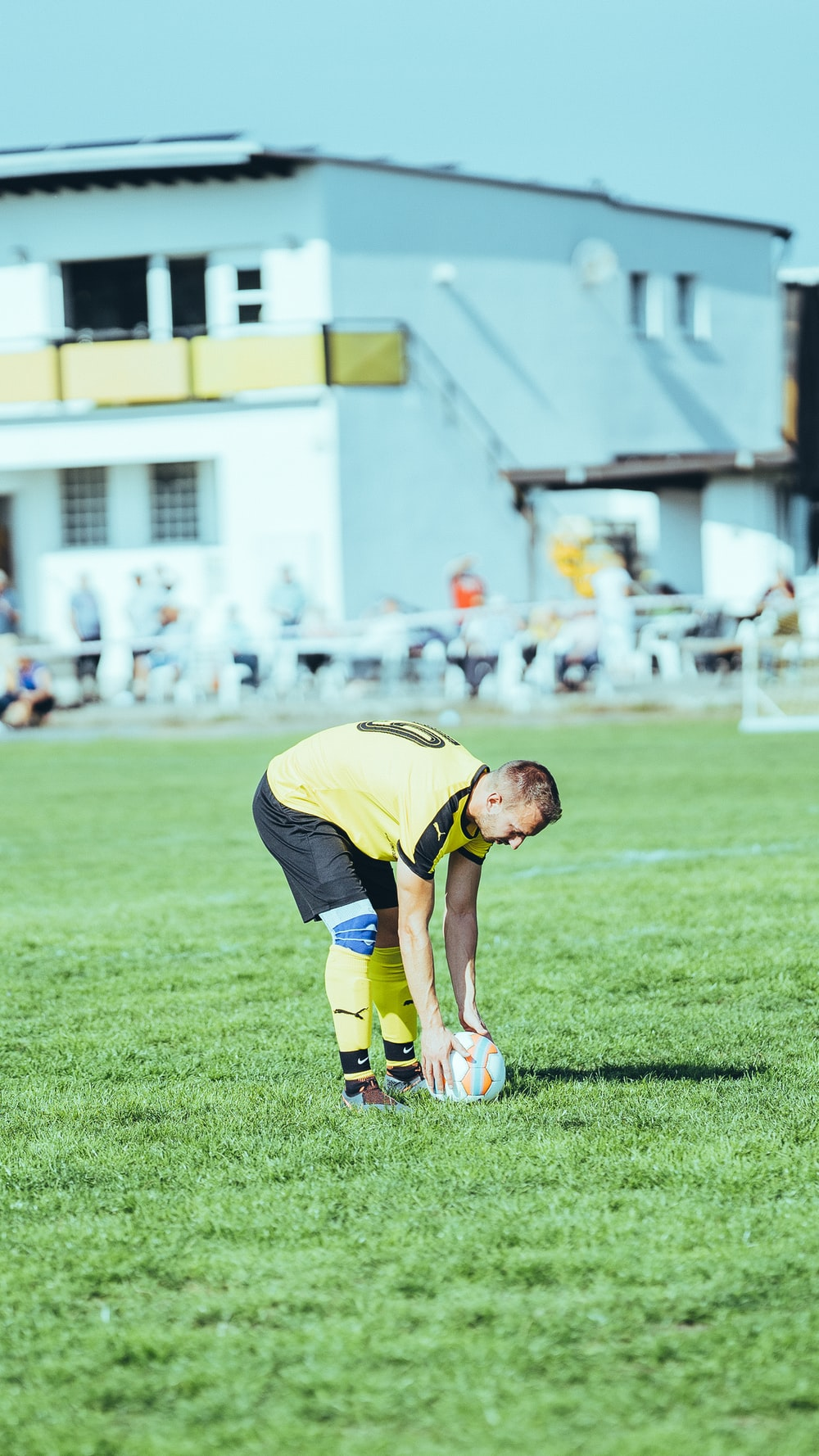 man in yellow shirt and black shorts playing soccer during daytime