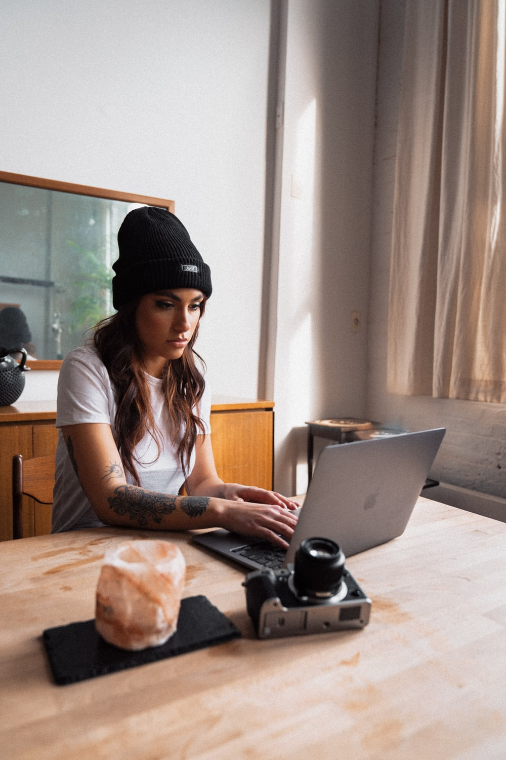 woman in black knit cap using macbook