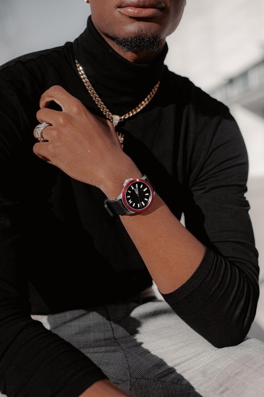 person wearing gold round analog watch