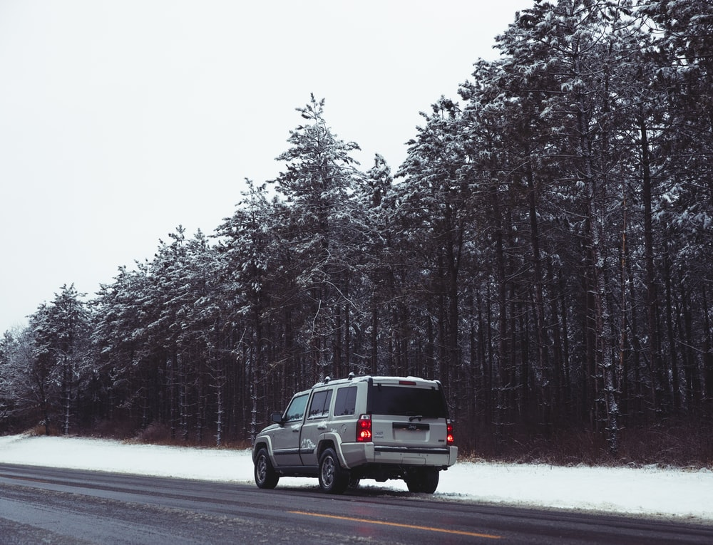 black suv on road between trees covered with snow during daytime