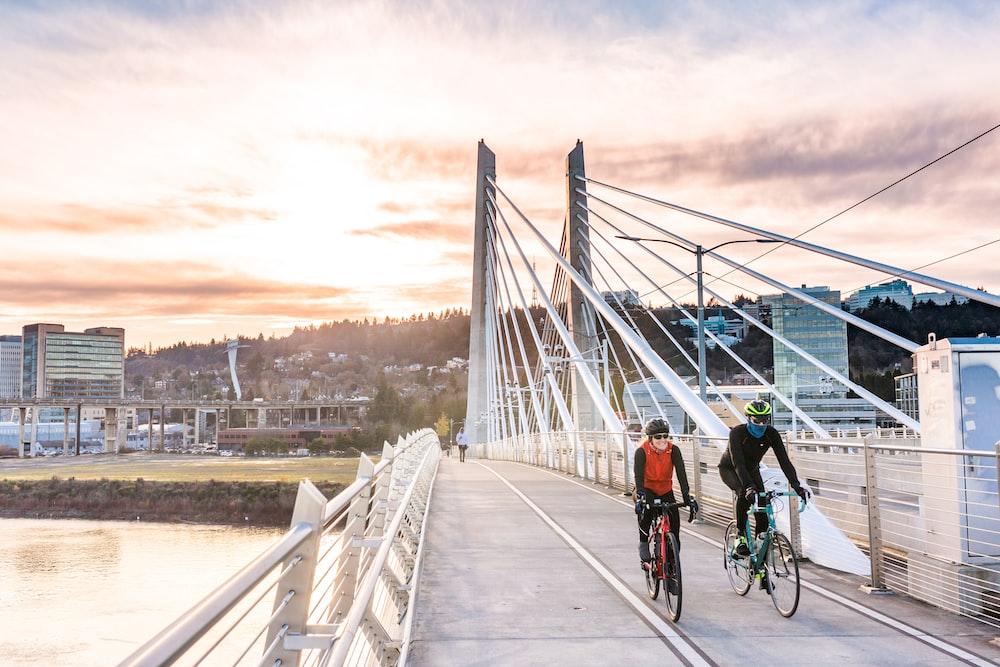 people riding bicycle on bridge during daytime