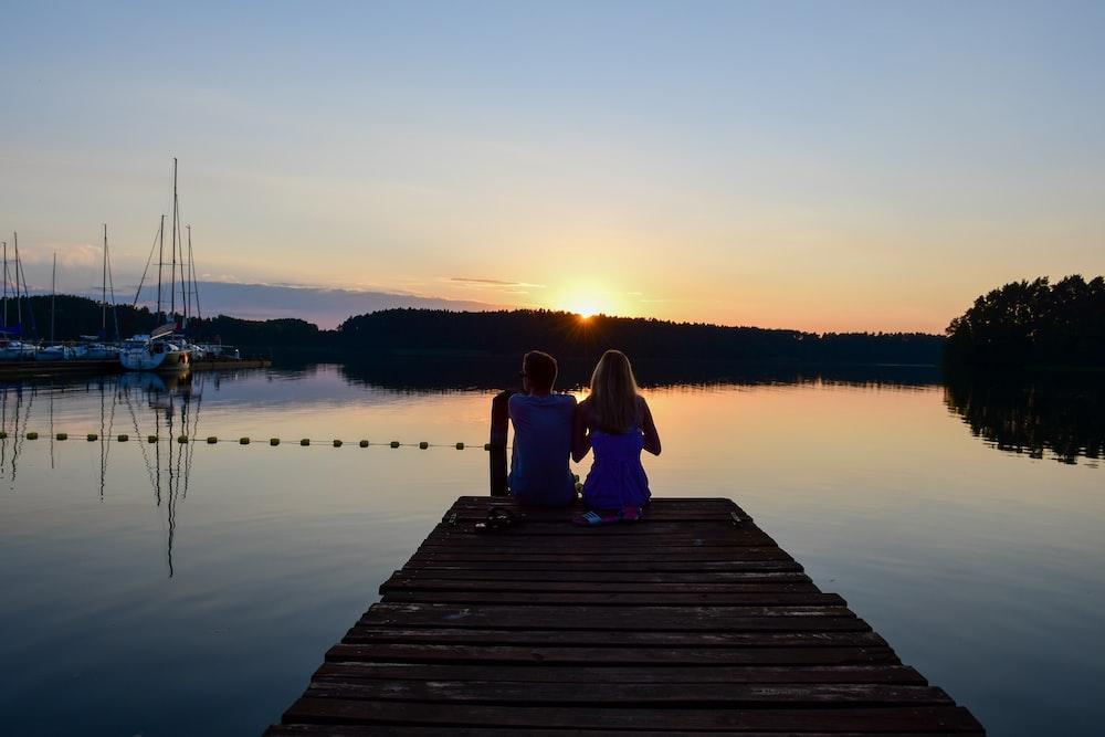 couple sitting on dock during sunset