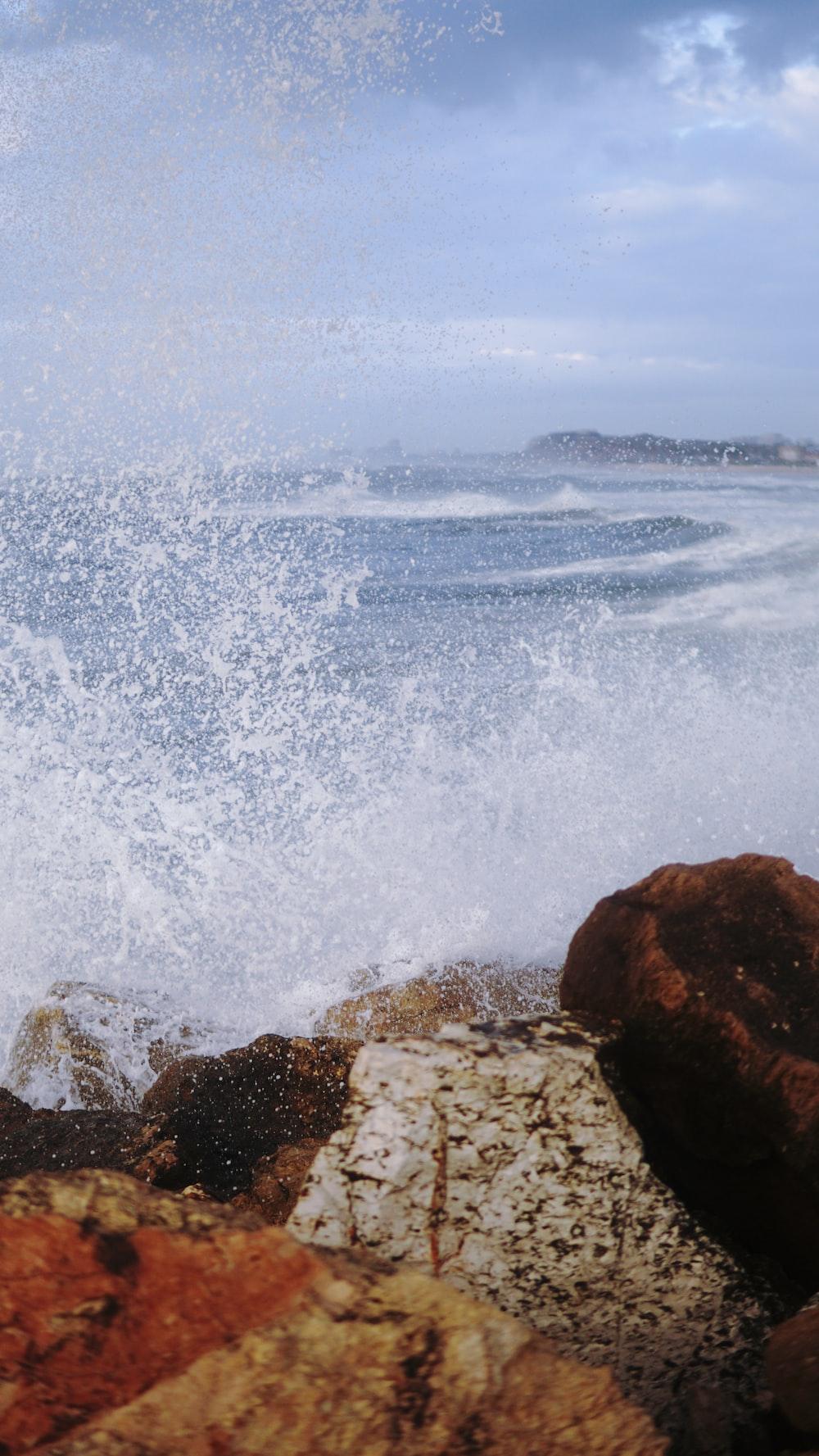 ocean waves crashing on brown rock