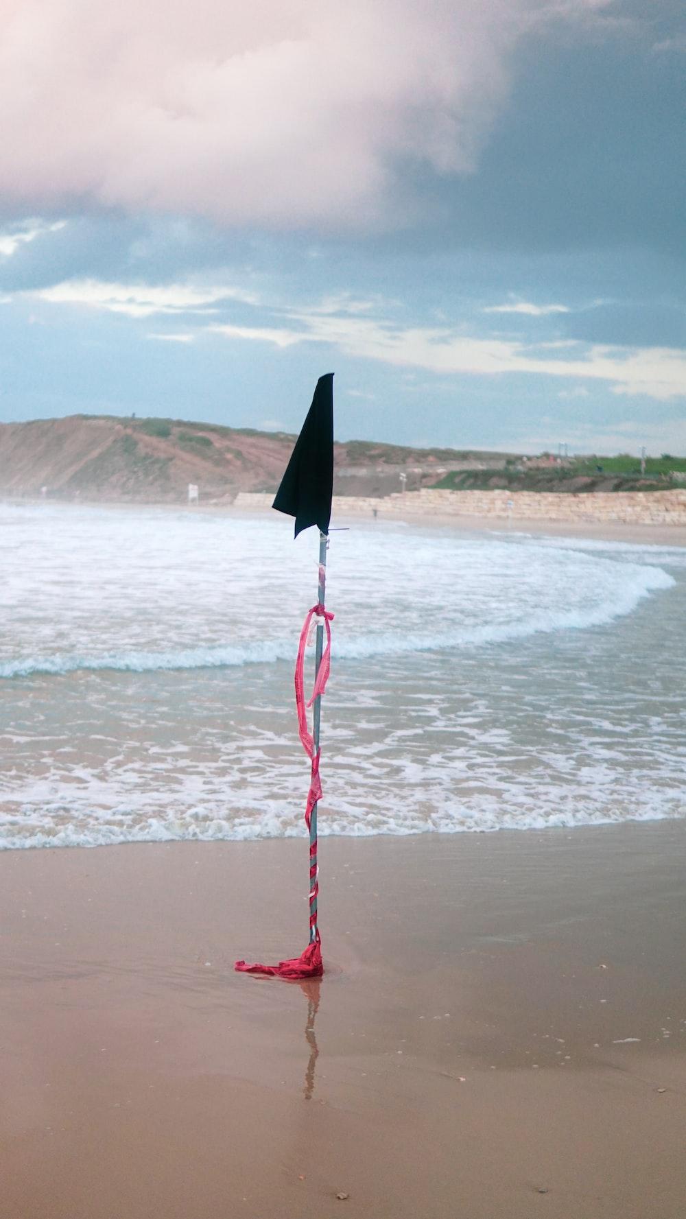 black flag on beach shore during daytime